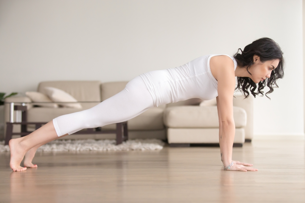 Young attractive woman in Plank pose at cozy living room